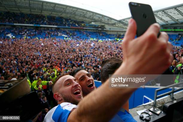 Anthony Knockaert and Jiri Skalak of Brighton Hove Albion celebrate with teammates in the stands after victory in the Sky Bet Championship match...