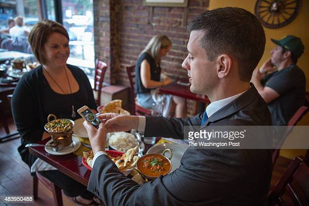 Anthony Lacey takes a picture of his food while he interviews and dines with Meredith Denbow at Jyoti in the Adams Morgan neighborhood of Washington...