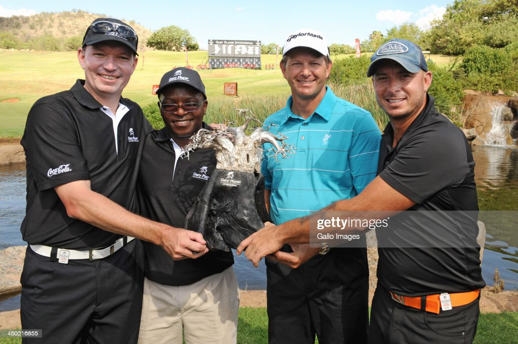 Anthony Leeming, Mike Dladla, professional golfer Retief Goosen and Herschelle Gibbs of Team Goosen pose with the trophy during the prizegiving ceremony for the Gary Player Invitational presented by Coca-Cola at The Lost City Golf Course on November 17, 2013 in Sun City, South Africa.