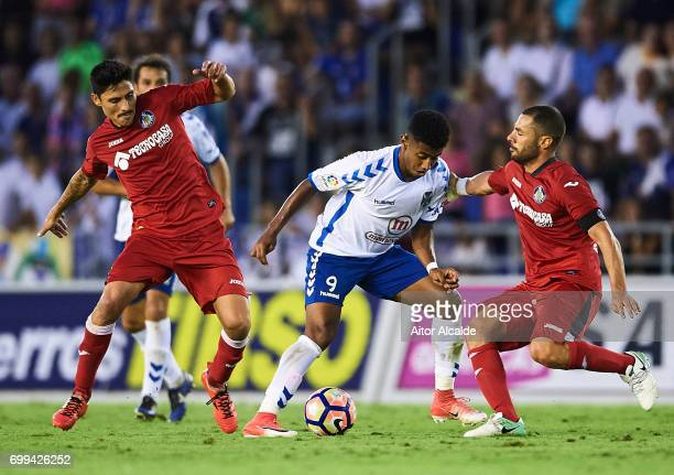 Anthony Lozano of CD Tenerife being fouled by Alejandro Faurlin of Getafe CF and Mehdi Laceng of Getafe CF during La Liga 2 play off round between CD...