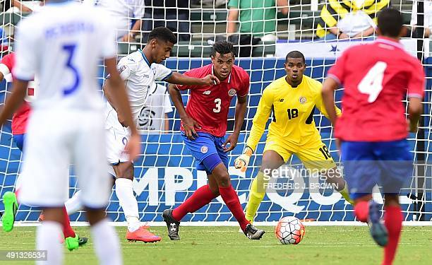 Anthony Lozano of Honduras winds up his shot to score for a 10 lead as Julio Cascante and goalkeeper Darryl Parker of Costa Rica look on on October 4...