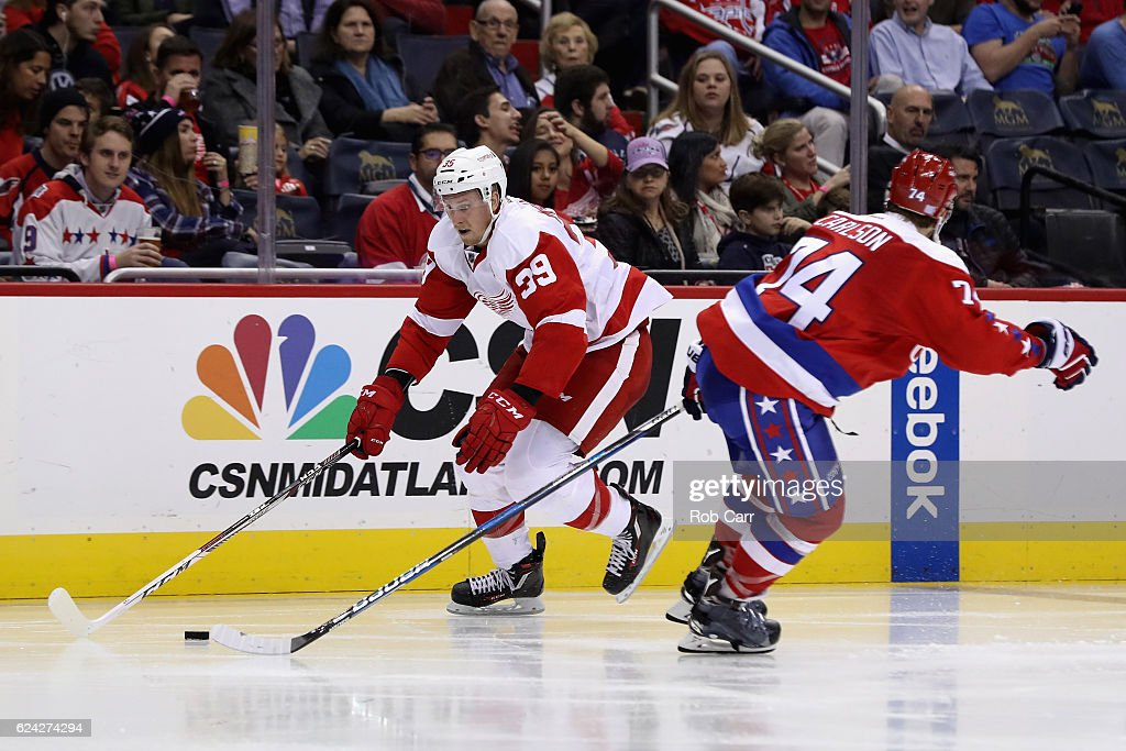 Anthony Mantha #39 of the Detroit Red Wings moves the puck in front of John Carlson #74 of the Washington Capitals in the third period at Verizon Center on November 18, 2016 in Washington, DC.