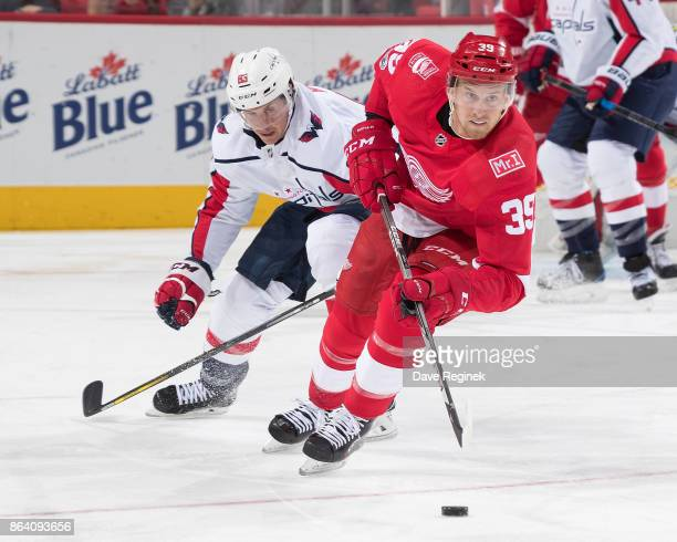 Anthony Mantha of the Detroit Red Wings skates up ice with the puck followed by Jay Beagle of the Washington Capitals during an NHL game at Little...