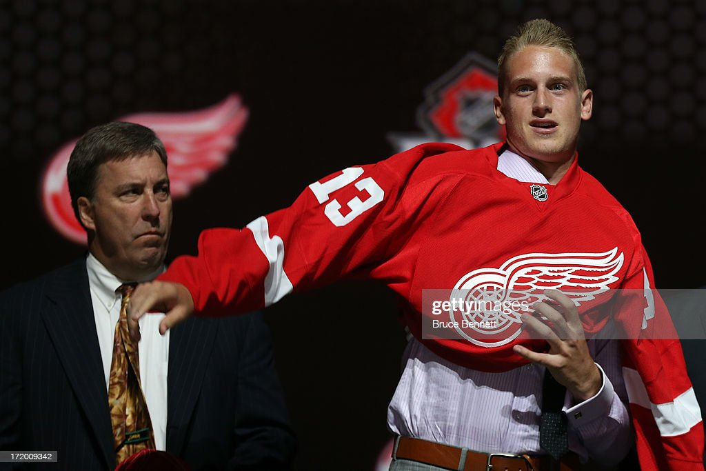 <a gi-track='captionPersonalityLinkClicked' href=/galleries/search?phrase=Anthony+Mantha&family=editorial&specificpeople=10136659 ng-click='$event.stopPropagation()'>Anthony Mantha</a> reacts puts on his jersey after being selected number twenty overall in the first round by the Detroit Red Wings during the 2013 NHL Draft at the Prudential Center on June 30, 2013 in Newark, New Jersey.
