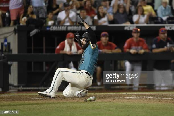 Anthony Marks of Coastal Carolina University slides safely into home and scores the goahead run against the University of Arizona during the Division...