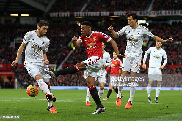 Anthony Martial of Man Utd shoots past Angel Rangel of Swansea and Jack Cork of Swansea during the Barclays Premier League match between Manchester...