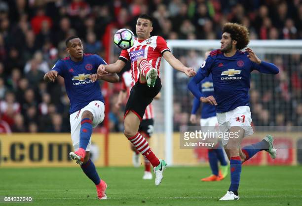 Anthony Martial of Manchester United and Marouane Fellaini of Manchester United attempt to win the ball from Dusan Tadic of Southampton during the...