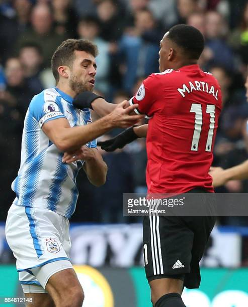 Anthony Martial of Manchester United clashes with Tommy Smith of Huddersfield Town during the Premier League match between Huddersfield Town and...