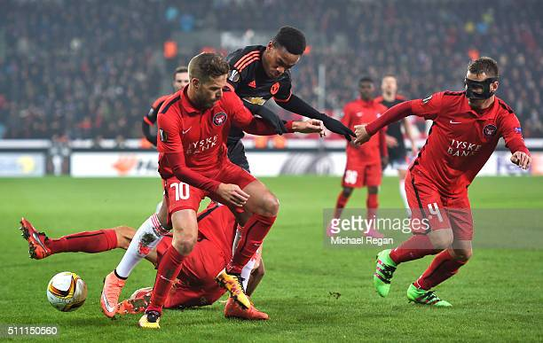 Anthony Martial of Manchester United controls the ball under pressure of Martin Pusic and Nikolay Bodurov of FC Midtjylland during the UEFA Europa...