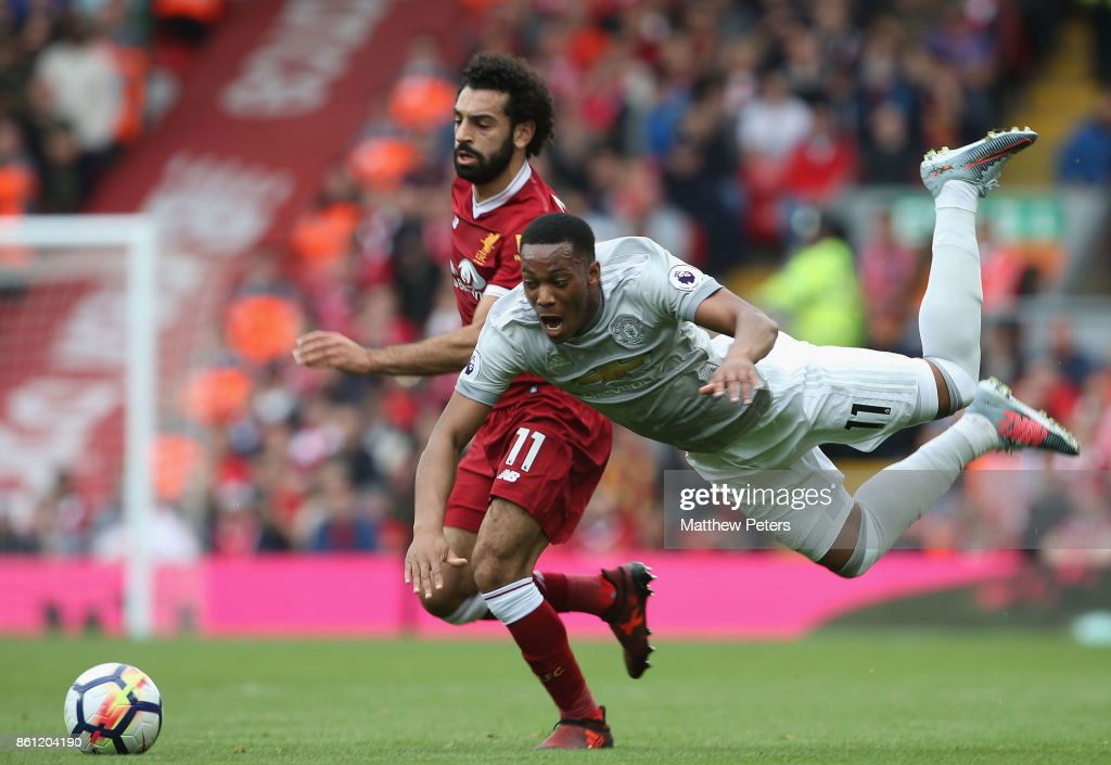 Anthony Martial of Manchester United in action with Mohamed Salah of Liverpool during the Premier League match between Liverpool and Manchester United at Anfield on October 14, 2017 in Liverpool, England.