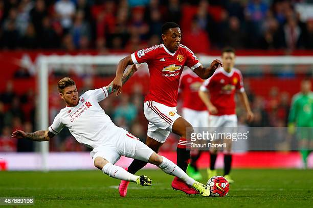 Anthony Martial of Manchester United is tackled by Alberto Moreno of Liverpool during the Barclays Premier League match between Manchester United and...