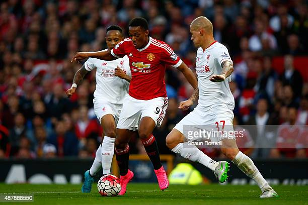 Anthony Martial of Manchester United takes on Nathaniel Clyne and Martin Skrtel of Liverpool during the Barclays Premier League match between...