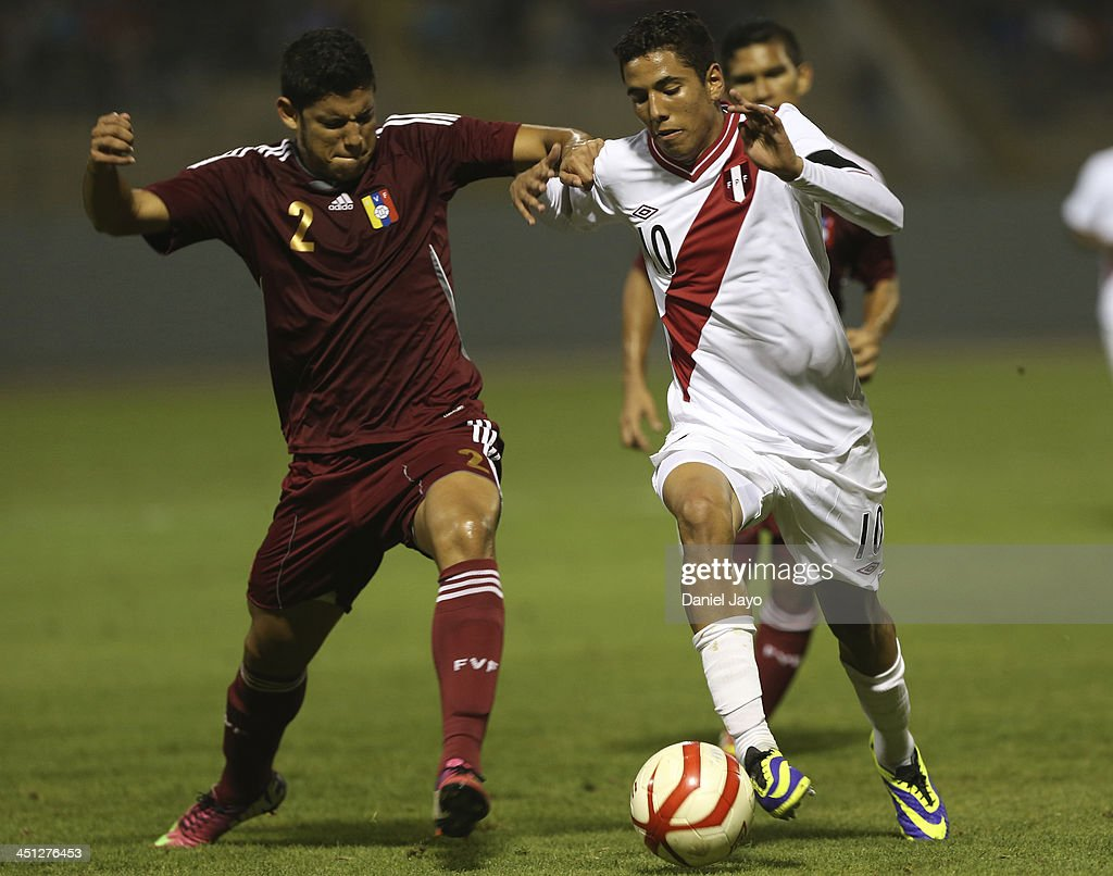 Anthony Matos, of Venezuela, (L) and Sergio Pena, of Peru, compete for the ball during a U18 match between Peru and Venezuela as part of the XVII Bolivarian Games Trujillo 2013 at Mansiche Stadium on November 21, 2013 in Lima, Peru.