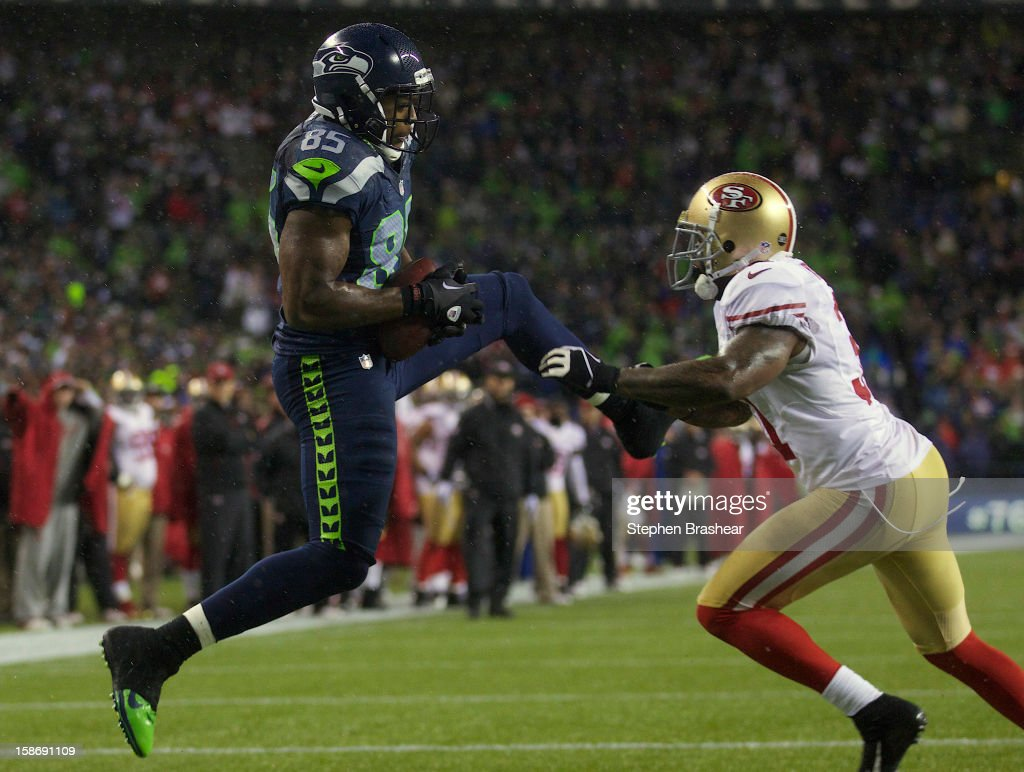 Anthony McCoy #85 of the Seattle Seahawks makes a touchdown catch against Donte Whitner #31 of the San Francisco 49ers during a game at CenturyLink Field on December 23, 2012 in Seattle, Washington.