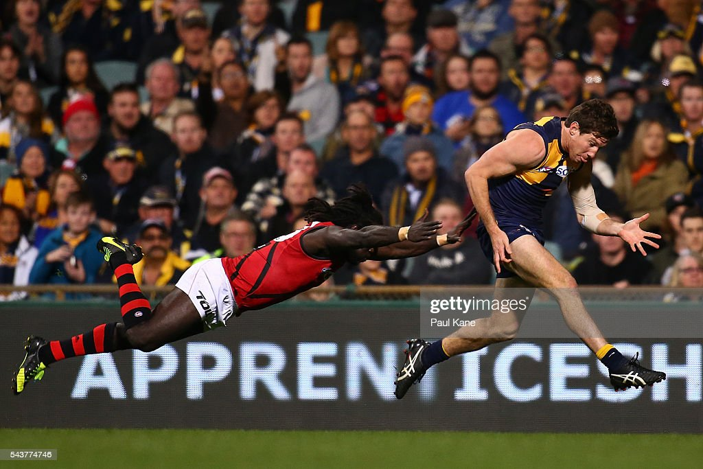 Anthony McDonald-Tipungwuti of the Bombers dives in an attempt to tackle Patrick McGinnity of the Eagles during the round 15 AFL match between the West Coast Eagles and the Essendon Bombers at Domain Stadium on June 30, 2016 in Perth, Australia.