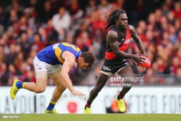 Anthony McDonaldTipungwuti of the Bombers kicks the ball from Luke Shuey of the Eagles during the round nine AFL match between the Essendon Bombers...