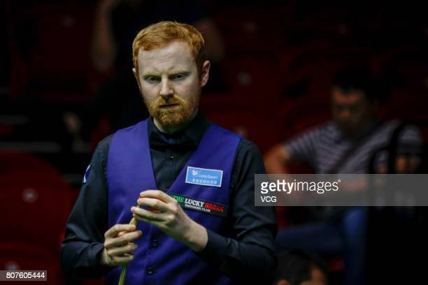 Anthony McGill of Scotland chalks the cue against Michael Georgiou of Cyprus and Antonis Poullos of Cyprus on day two of 2017 Snooker World Cup at...