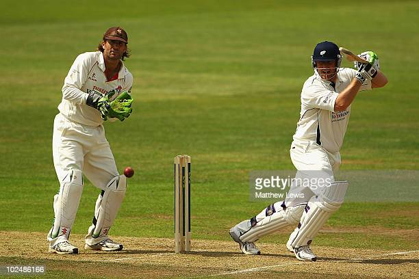 Anthony McGrath of Yorkshire hits the ball towards the boundary as Luke Sutton of Lancashire looks on during the LV County Championship match between...