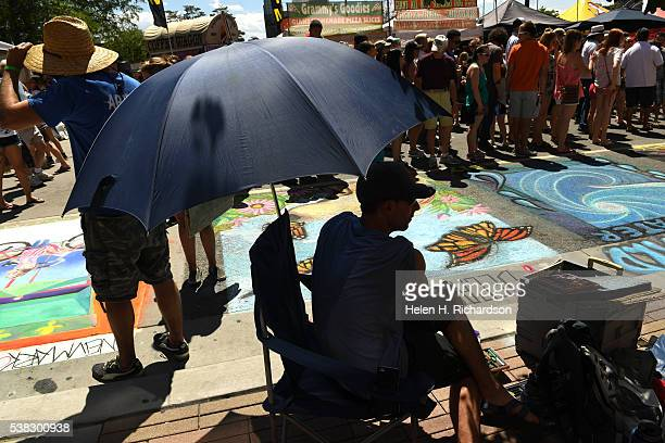 Anthony Menzor stays cool under an umbrella while he watches his girlfriend Stefanie Wachter work on her artwork during the 14th annual chalk art...