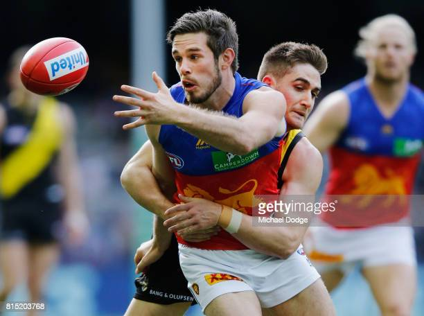 Anthony Miles of the Tigers tackles Ryan Bastinac of the Lions during the round 17 AFL match between the Richmond Tigers and the Brisbane Lions at...