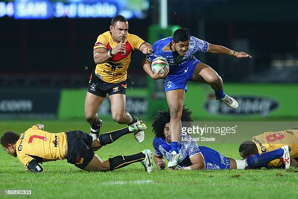 Anthony Milford of Samoa ihurdles over Ray Thompson with Paul Aiton of Papua New Guinea in pursuit during the Rugby League World Cup Group B match...
