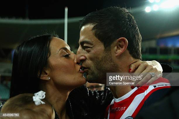 Anthony Minichiello of the Roosters embraces his wife Terry Biviano and daughter after winning the round 26 NRL match between the Sydney Roosters and...
