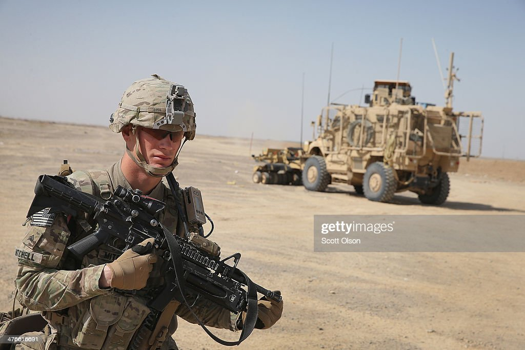 SGT Anthony Mitchell from Greensboro, North Carolina with the U.S. Army's 4th squadron 2d Cavalry Regiment prepares to patrol through a village during on March 3, 2014 near Kandahar, Afghanistan. President Obama recently ordered the Pentagon to begin contingency planning for a pullout from Afghanistan by the end of 2014 if Afghanistan President Hamid Karzai or his successor refuses to sign the Bilateral Security Agreement.