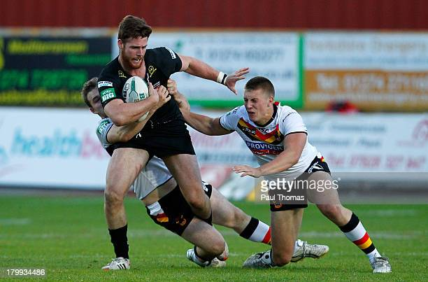 Anthony Mullally of Huddersfield is tackled by Ben Evans and Alex Mellor of Bradford during the Super League match between Bradford Bulls and...