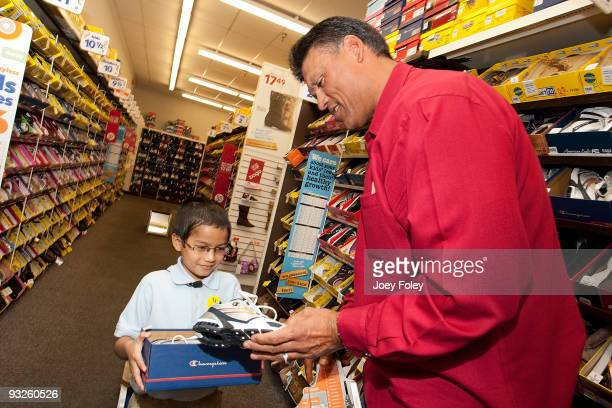 Anthony Munoz helps a young kid pick out a pair of shoes at Payless ShoeSource on November 20 2009 in Cincinnati Ohio