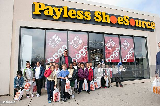 Anthony Munoz poses with children holding their new shoes outside at the Payless ShoeSource on November 20 2009 in Cincinnati Ohio
