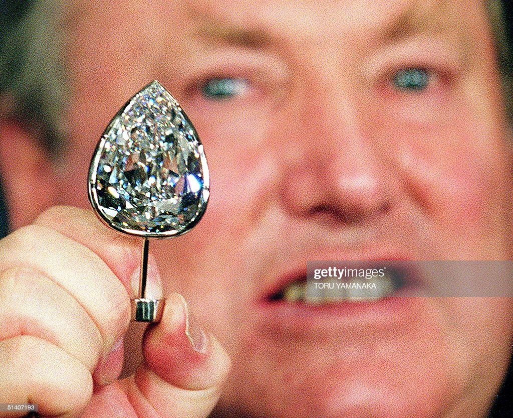 Anthony Oppenheimer, president of Central Selling Organisation of the world's largest diamond mining and marketing company De Beers, unveils the world's biggest pear-shaped diamond 'Millennium Star' at the British embassy in Tokyo 13 October 1999. The 203-carat diamond will be exhibited for the public to celebrate the year 2000 from 01 January at the Millennium Dome, which is under construction at Greenwich in London. AFP PHOTO/Toru YAMANAKA