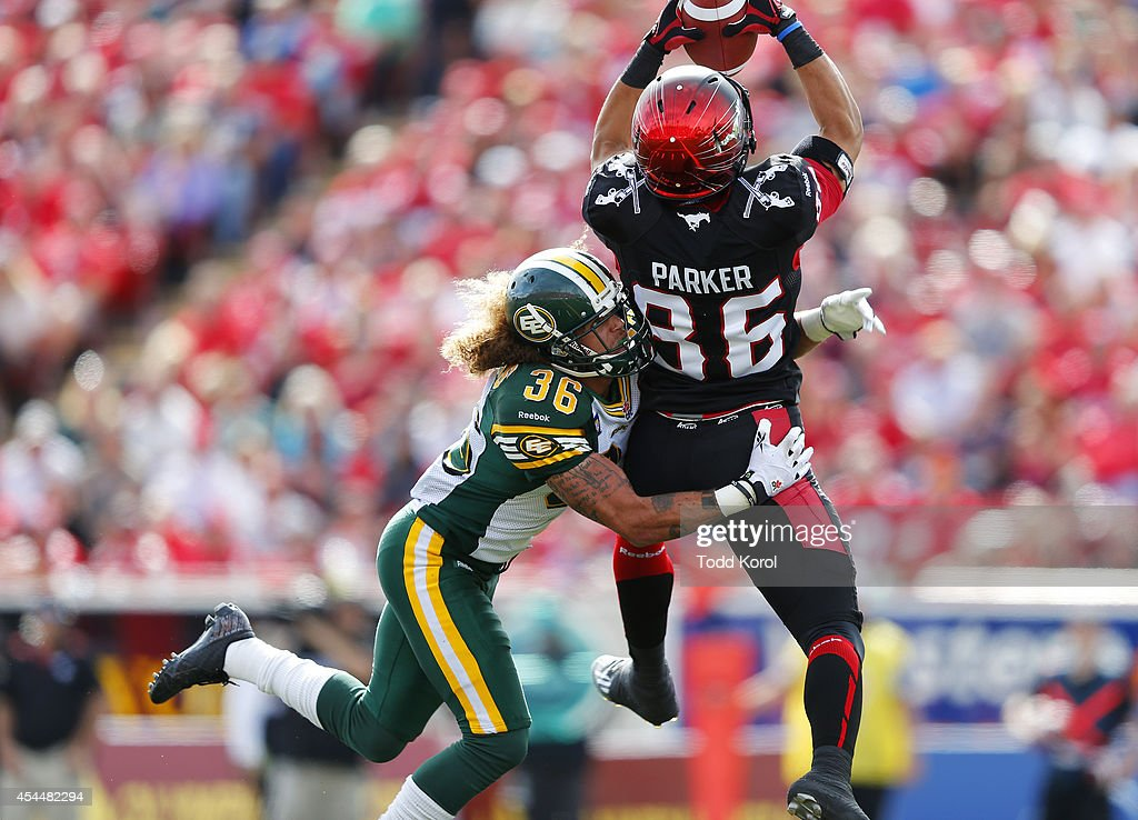 Anthony Parker #86 of the Calgary Stampeders catches the ball for a touchdown while Aaron Grymes #36 of the Edmonton Eskimos catches him during the first half of their CFL football game September 1, 2014 at McMahon Stadium in Calgary, Alberta, Canada.