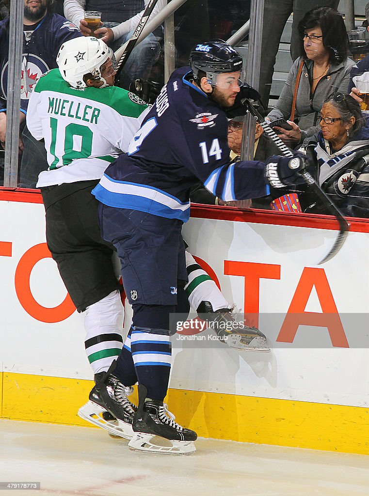 Anthony Peluso of the Winnipeg Jets checks Chris Mueller of the Dallas Stars into the boards during second period action at the MTS Centre on March...
