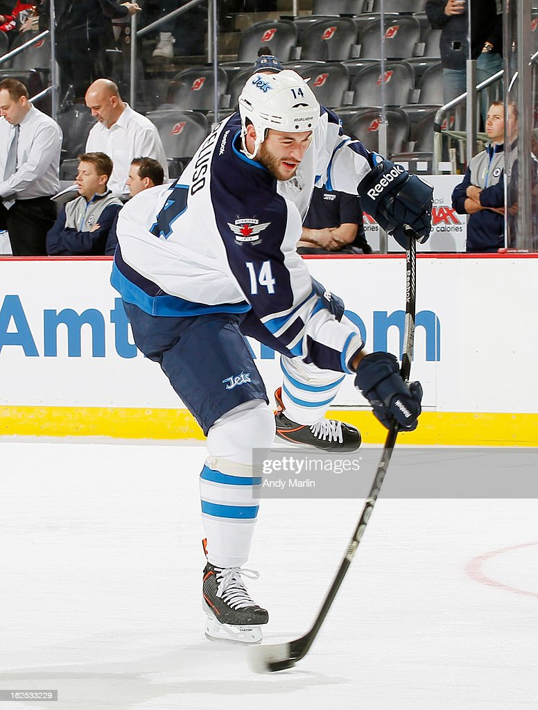 Anthony Peluso #14 of the Winnipeg Jets fires a shot during pregame warmups against the New Jersey Devils at the Prudential Center on February 24, 2013 in Newark, New Jersey.