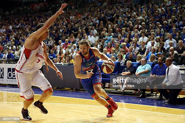 Anthony Petrie of the 36ers takes on Oscar Forman of the Wildcats as the 36ers bench looks on during the round eight NBL match between the Adelaide...