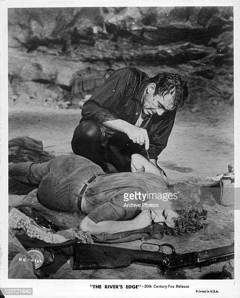 Anthony Quinn cuts the arm of Debra Paget with a scalpel in a scene from the film 'The River's Edge' 1957