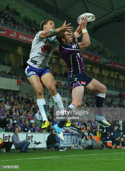 Anthony Quinn of the Storm is challenged for the ball by Sandor Earl of the Raiders during the round 18 NRL match between the Melbourne Storm and the...