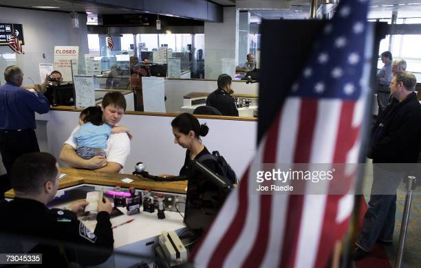 Anthony Ramos a Customs and Border Protection officer checks Chris Layman Katy Layman 21 months old and Natalie Layman in at the passport control...
