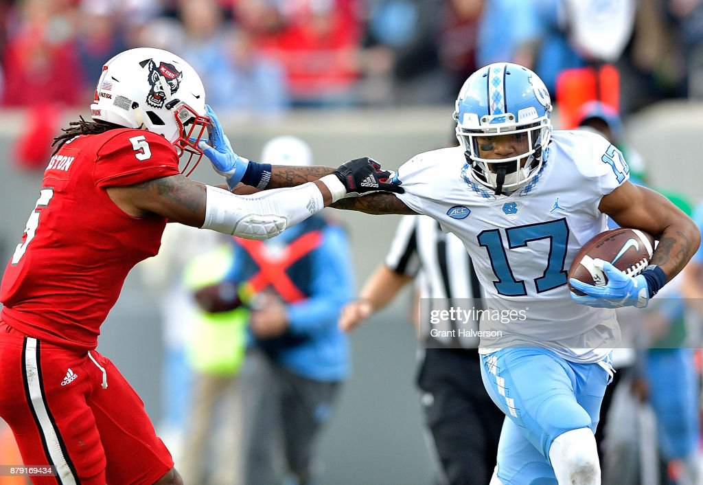 Anthony Ratliff-Williams #17 of the North Carolina Tar Heels stiff-arms Johnathan Alston #5 of the North Carolina State Wolfpack during their game at Carter Finley Stadium on November 25, 2017 in Raleigh, North Carolina.