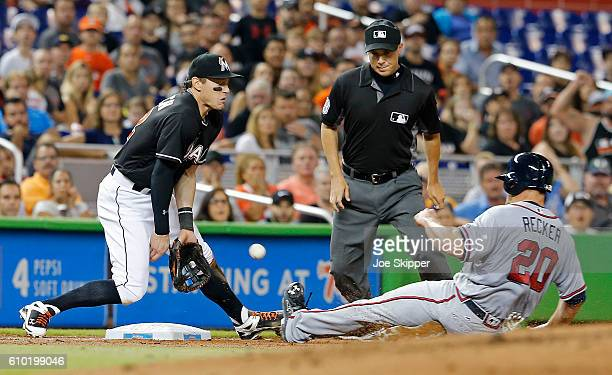 Anthony Recker of the Atlanta Braves is safe at third as Derek Dietrich of the Miami Marlins can't handle the late throw in the second inning at...