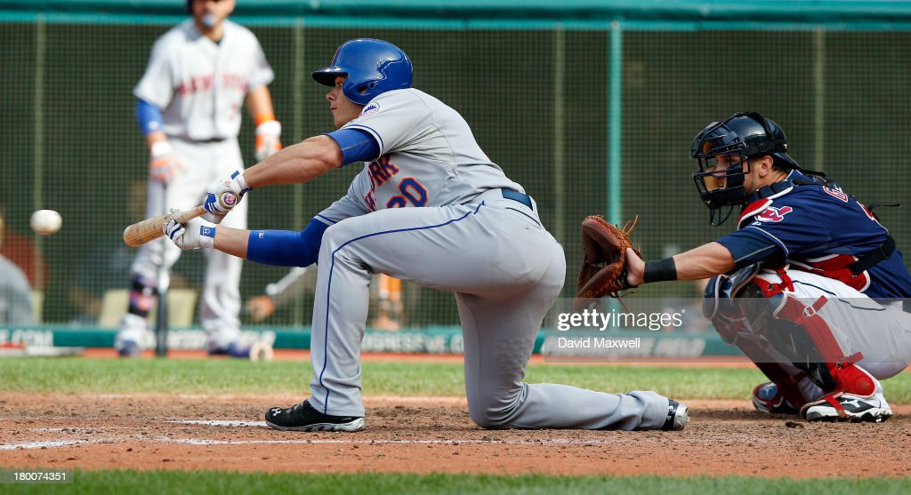 Anthony Recker #20 of the New York Mets lays down a sacrifice bunt against the Cleveland Indians as Indians catcher <a gi-track='captionPersonalityLinkClicked' href=/galleries/search?phrase=Yan+Gomes&family=editorial&specificpeople=9004037 ng-click='$event.stopPropagation()'>Yan Gomes</a> #10 looks on during the eighth inning of their game on September 8, 2013 at Progressive Field in Cleveland, Ohio. The Mets defeated the Indians 2-1.