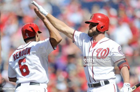 Anthony Rendon of the Washington Nationals celebrates with Kevin Frandsen after scoring in the first inning against the Philadelphia Phillies at...