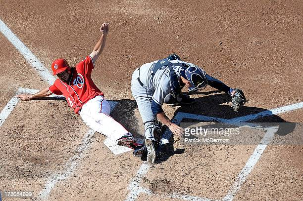 Anthony Rendon of the Washington Nationals is out at home plate as he collides with Yasmani Grandal of the San Diego Padres during the third inning...