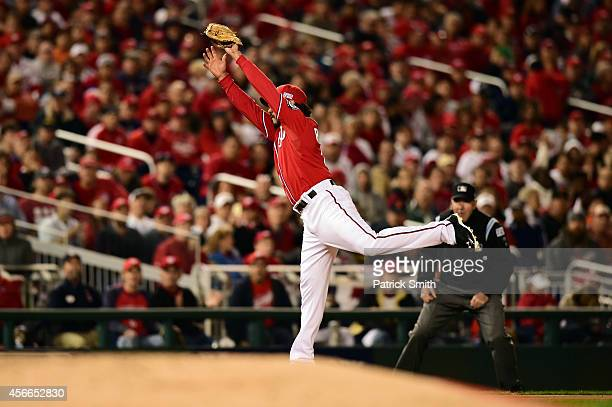 Anthony Rendon of the Washington Nationals stretches to catch a ball hit by Buster Posey of the San Francisco Giants in the seventh inning during...