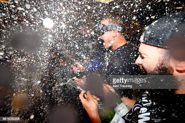 Anthony Rizzo and Jake Arrieta of the Chicago Cubs celebrate with their teammates in the clubhouse after winning Game 5 of the National League...