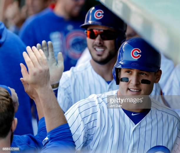 Anthony Rizzo of the Chicago Cubs and Kris Bryant are congratulated in the dugout after scoring on a wild pitch during the eighth inning against the...