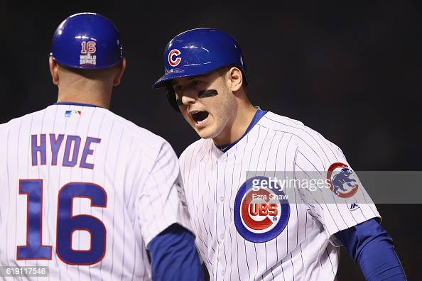 Anthony Rizzo of the Chicago Cubs celebrates with first base coach Brandon Hyde after hitting a single in the first inning against the Cleveland...