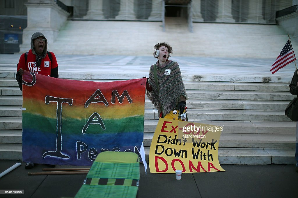 Anthony Robledo (L) and Sally Wilson yawn while holding a banner in front of the U.S. Supreme Court, on March 26, 2013 in Washington, DC. Today the high court is scheduled to hear arguments in California's proposition 8, the controversial ballot initiative that defines marriage as between a man and a woman.