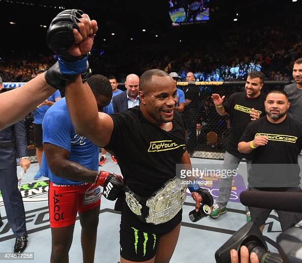 Anthony 'Rumble' Johnson places the belt on Daniel Cormier after their UFC light heavyweight championship bout during the UFC 187 event at the MGM...