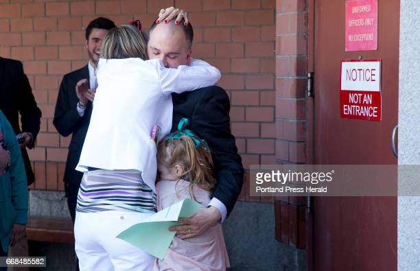 Anthony Sanborn hugs his wife Michelle Sanborn and his cousin's daughter Xienna Hanscome moments after walking out the door of Cumberland County Jail...